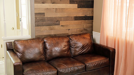 Brown Leather Sofa In Front Of Completed DIY Wood Plank Wall