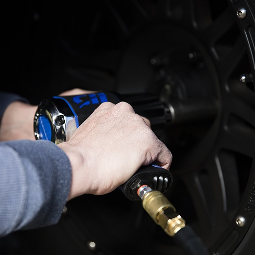 Man using Campbell Hausfeld 1/2-Inch Impact Wrench on hub caps 2